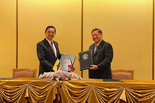 Department of Finance (DOF) Secretary Carlos Dominguez of the Philippines and Yang Berhormat Dato Seri Setia Dr. Awang Haji Mohd Amin Liew bin Abdullah, the Minister at the Prime Minister%u2019s Office and Minister of Finance and Economy II of Brunei Darussalam, hold their copies of the double taxation agreement they signed on behalf of their respective governments on July 16, 2021 in Bruneis capital city of Bandar Seri Begawan. / DOF
